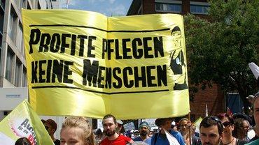 """Plakat mit Aufschrift """"Profite pflegen keine Menschen"""